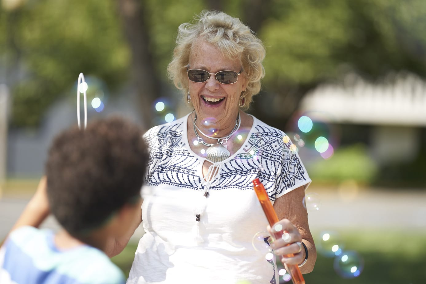 Retirement community photography. Smiling resident playing with grandkids